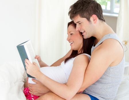 Portrait of a young pregnant woman and of her husband reading a book photo