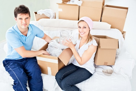 Smiling young couple unpacking boxes with glasses photo