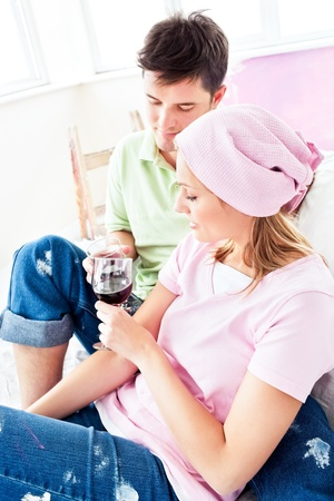 paintrush: Happy couple drinking wine on the sofa after painting their new room