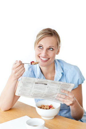 Glowing businesswoman having breakfast and reading a newspaper photo