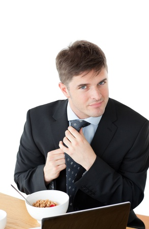 Elegant businessman having breakfast and touching his tie in front of his laptop photo