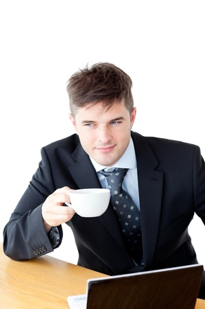 Attractive businessman holding a cup of coffee in front of his laptop photo