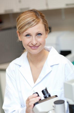 Smiling female scientist using a microscope Stock Photo - 10243627
