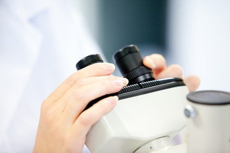 Close-up of a female scientist looking through a microscope Stock Photo - 10243674