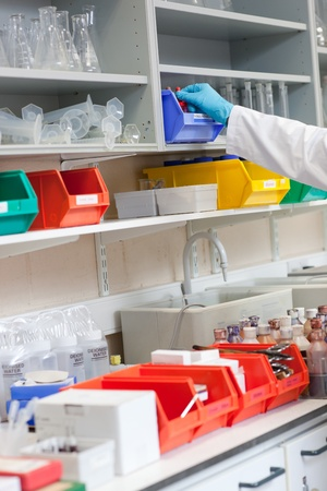 Close-up of a scientist taking something on the shelf Stock Photo - 10244102