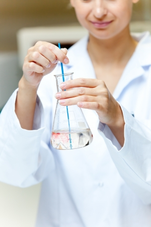 Portrait of a female scientist shaking liquid in an erlenmeyer photo