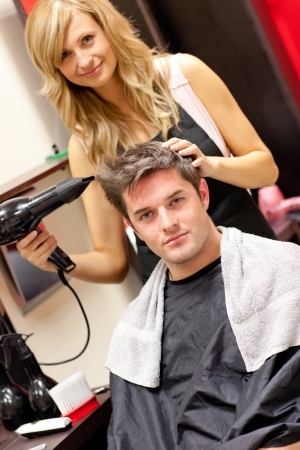 Professional female hairdresser drying her customer photo