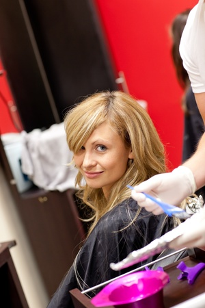 Smiling blond woman drying her hair Stock Photo - 10254439