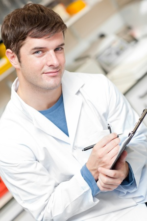 scientists: Handsome scientist holding a clipboard and smiling at the camera Stock Photo