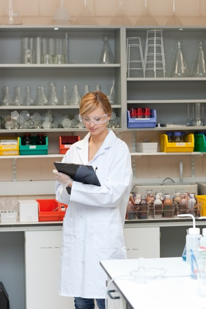 Concentrated female scientist writing on her clipboard Stock Photo - 10245036