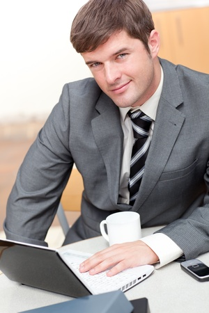 Busy businessman with a laptop, a cellphone and a mug sitting at his desk photo