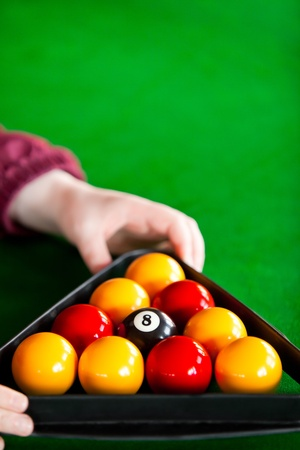 Close-up of a snooker player placing balls with triangle photo