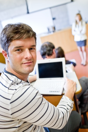 Close-up of a bright male student using a laptop during a university lesson photo