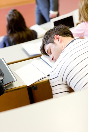 Asleep male student during an university lesson photo