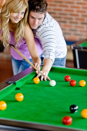 billiards tables: Affectionate boyfriend learning his girlfriend how to play pool Stock Photo