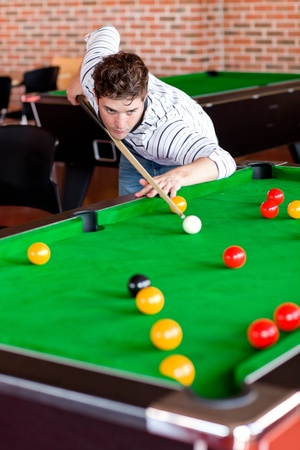 Concentrated young man playing snooker photo