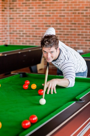 assertive: Assertive young man playing snooker