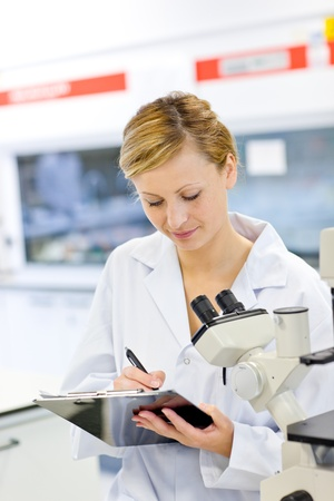 Serious female scientist writing on her clipboard in front of a microscope photo