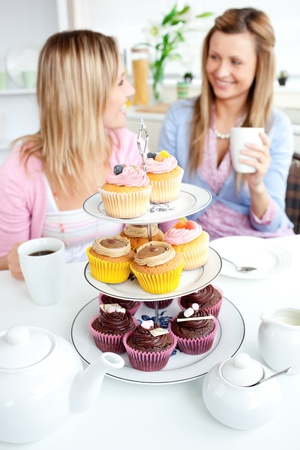 Two cute friends eating cupcakes sitting in the kitchen at home photo