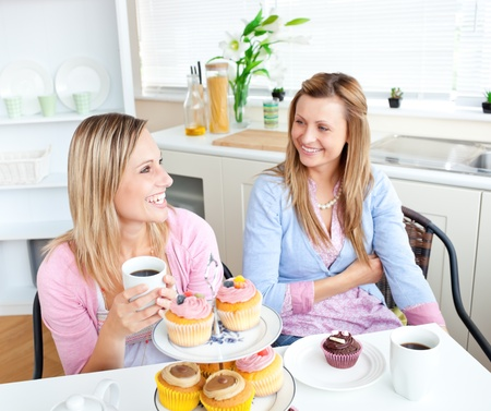 Female friends with cakes and coffee speaking together in the kitchen photo