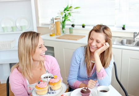 Laughing women eating cupcakes and drinking coffee sitting in the kitchen photo