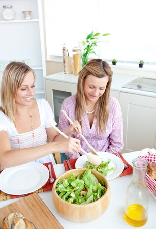 Two healthy women eating salad in the kitchen during lunchtime at home photo