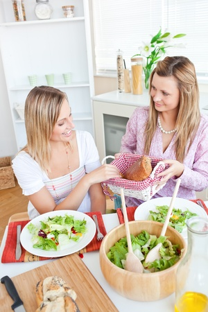Young woman giving bread to her friend while eating salad in the kitchen photo