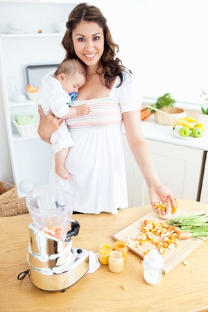 Smiling mother holding her sleeping child while preparing carrot using a blender photo