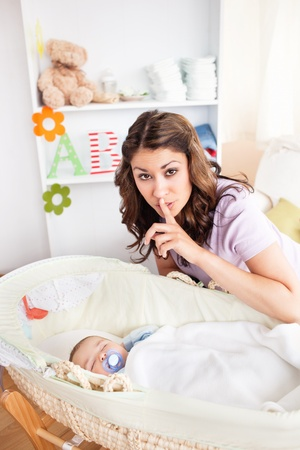 nap: Attentive mother doing hush sign to the camera whle her baby is sleeping in his cradle Stock Photo