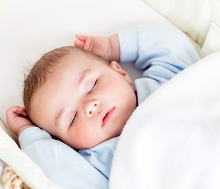 Portrait of a peaceful baby sleeping in his cradle at home photo