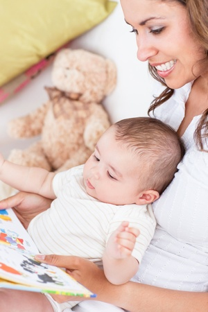 Portrait of joyful mother reading a book to her baby sitting in the living-room photo