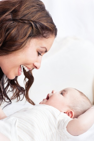 tender tenderness: Portrait of an adorable mother playing with her baby sitting in the sofa at home