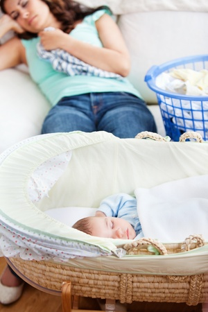 Cute baby sleeping in his cradle with his mother lying on the couch in the background photo