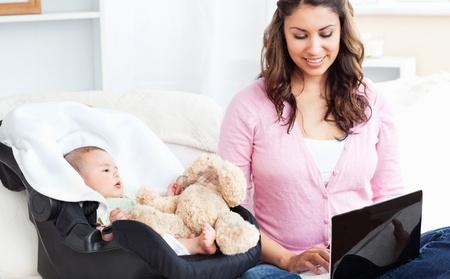 Helle Mutter arbeitet an einem Laptop mit ihrem Baby neben ihr sa� mit seinem Teddy-B�r Lizenzfreie Bilder