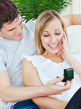 propose: Happy woman receiving a wedding ring during a proposal at home