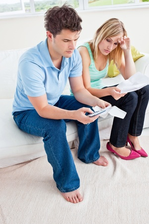 Stressed young couple calculating bills sitting in the living-room Stock Photo - 10254472