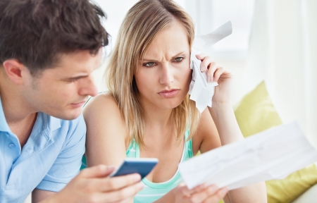 Focused couple calculating bills using a calculator sitting on the sofa Stock Photo - 10254394