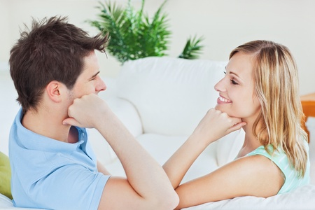 Young couple playing to look at each other sitting on the sofa photo