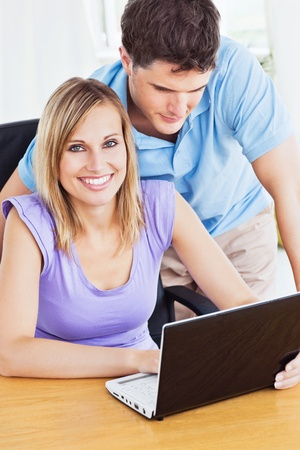 Portrait of a cheerful woman and her attentive boyfriend using a laptop photo