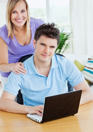Young man using a laptop sitting at a table with his girlfriend behind both smiling at the camera photo