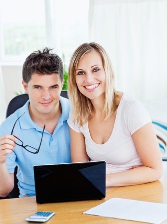 Portrait of a cheerful couple using a laptop sitting together at a table photo