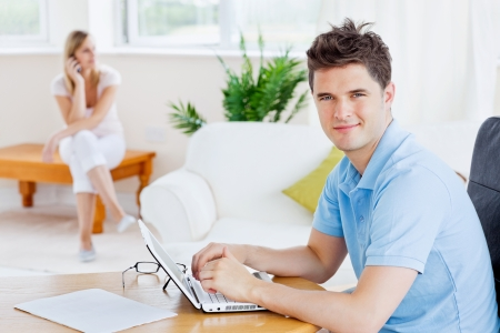 Happy man using his laptop sitting at a table with his girlfriend on the phone in the background photo