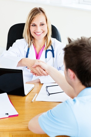 Friendly female doctor shaking hands with patient sitting in her office photo