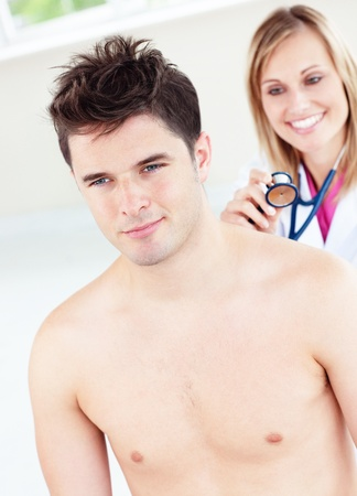 Cute female doctor feeling the breathing of a patient using her stethoscope photo