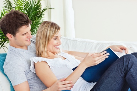 Cute couple browsing a book lying on the sofa photo