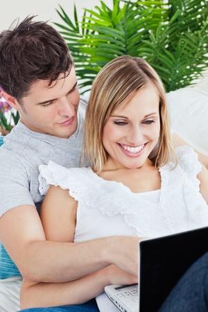 Joyful woman using a laptop lying on the sofa with her boyfriend photo