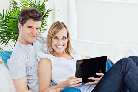 Young happy couple lying on the sofa with laptop smiling at the camera photo