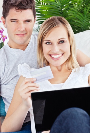 Glad couple buying online with credit card and laptop laying on the sofa photo