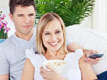 Portrait of an attractive couple with pop-corn and remote relaxing on the sofa photo