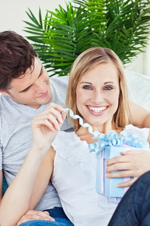 Happy woman unwrapping a present lying on the sofa with her boyfriend Stock Photo - 10254492